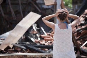Woman in front of burned out house